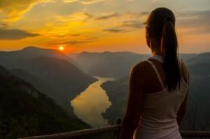 Mujer-observando-el-atardecer-desde-la-montaña