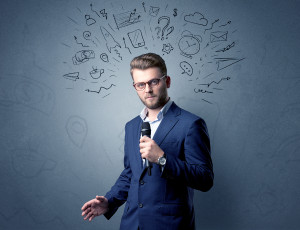 Businessman speaking into microphone with mixed doodles over his head